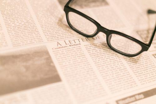 英字新聞と眼鏡の画像
